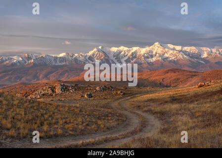 Schönen Herbst Sonnenaufgang mit einem gewundenen Feldweg auf einem Berg vor dem Hintergrund der Berge bedeckt mit Wald und Schnee, blauer Himmel und Cl - Stockfoto