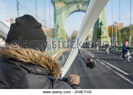 Ingwer pedal Taxi rider Kreuzung Hammersmith Bridge in West London, Großbritannien - Stockfoto