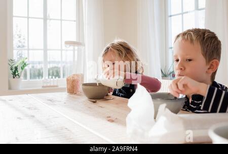 Bruder und Schwester essen Frühstück zu Hause vor der Schule Stockfoto