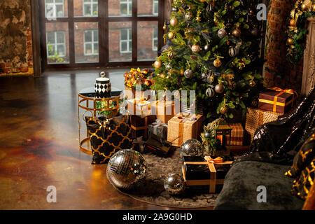 In der Nähe eines Weihnachtsbaumes mit goldenen Kugeln dekoriert. Unter dem Weihnachtsbaum eine große Anzahl der Weihnachtsgeschenke. Weihnachten Konzept. Eine riesige - Stockfoto