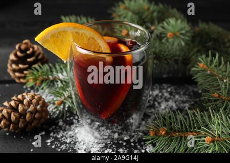 Glas leckeren Glühwein mit Orange auf Holz- Hintergrund eingerichtet, in der Nähe - Stockfoto