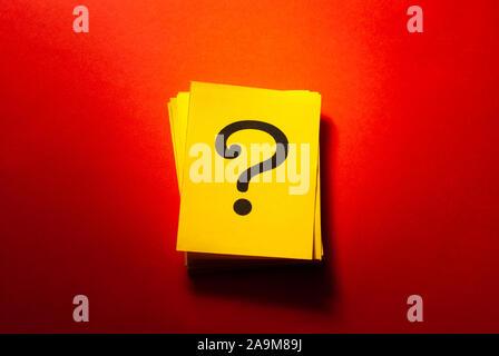 Gelbe Karten mit gedruckten Fragezeichen über eine bunte Roter Hintergrund mit Kopie Raum gestapelt - Stockfoto