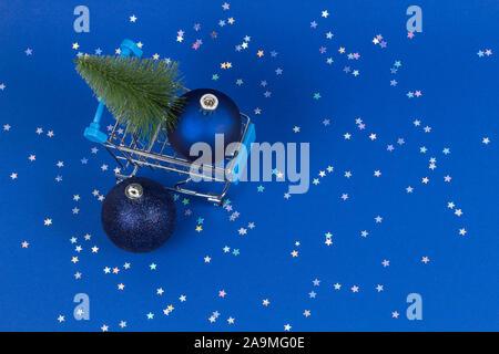 Mini Warenkorb mit kleinen Weihnachtsbaum und Marine Weihnachtsdekoration christbaumkugel Kugeln auf blauem Hintergrund mit Silber glitzer sterne - Stockfoto