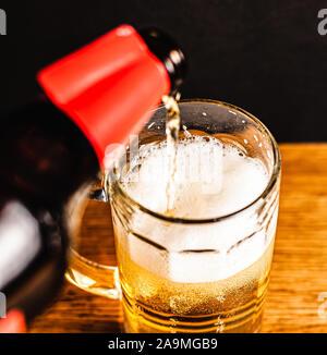 Kaltes Bier mit Schaum in einem Becher, auf einem Holztisch und einen dunklen Hintergrund mit leeren Platz für ein Logo oder Text. Der Foto Becher kalten schäumendem Bier close-up - Stockfoto