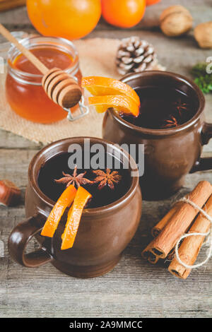 Heißer Glühwein mit Orange, Zimt, Honig und Anis auf Holz- Hintergrund. - Stockfoto