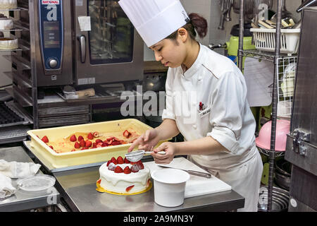 Eine japanische Frau Konditor Dekorieren ein Kuchen mit Puderzucker. - Stockfoto