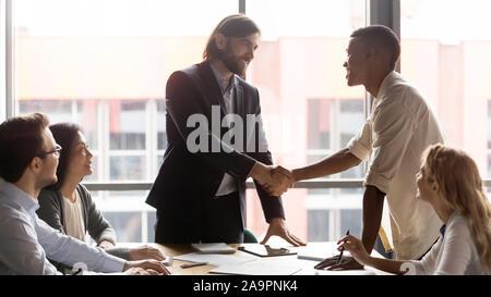 Lächelnd team leader Händeschütteln mit glücklichen afrikanische amerikanische Mitarbeiter. - Stockfoto