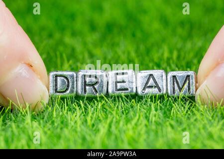 Nahaufnahme auf Wort Traum in Metall Buchstaben auf Gras gelegt geschrieben und zwischen die Finger einer Frau. Konzept der Sehnsucht, Hoffnung Hintergrund - Stockfoto