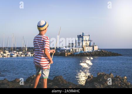 Rückansicht eines jungen Fischer mit mit der Angelrute in der Hand auf das Meer. Sailor Boy mit Wolle Gap und eine gestreifte T-Shirt mit einem Sommer - Stockfoto