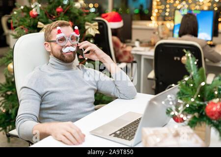 Glückliche junge Unternehmer in xmas Brillen telefonieren Business Partner - Stockfoto