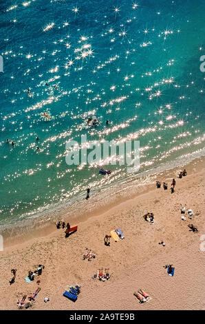 Sonnenlicht funkelt aus dem Pazifischen Ozean bei am Rande des berühmten Waikiki Beach, ein beliebtes Ziel für Urlauber, die in die Hauptstadt Honolulu auf Oahu ist eine der acht Hauptinseln, die Teil der tropischen Hawaii, USA kommen. Diese luftaufnahme zeigt nur einen kleinen Teil der Waikiki Strand, zwei Meilen (3,2 Kilometer) lang und eigentlich hat acht Abschnitte mit einzelnen Strand Namen. Mehr bevölkert sind die Sand und Walking Promenaden vor historischen und Hochhäusern entlang der gewundenen Küste. - Stockfoto