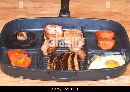 Frühstück pan für zwei Personen. Warmes Frühstück einschließlich Pilze, Würstchen, Speck, Spiegelei und Tomaten, auf dem hölzernen Küchentisch. - Stockfoto