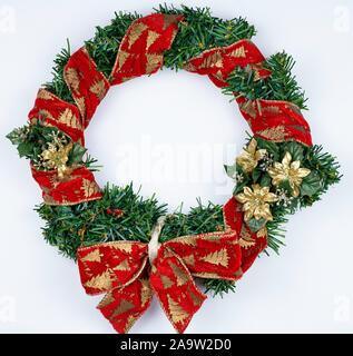 Weihnachten Kranz auf weißem Hintergrund. Red Ribbon auf grünem künstlichen Kiefer und roten Bogen, goldene Blumen. - Stockfoto
