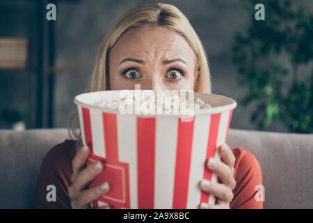 Nahaufnahme der ziemlich lustig lady Essen popcorn Fernsehen Horror Film Augen voller Angst ausblenden Gesicht angst Sofa casual Outfit - Stockfoto