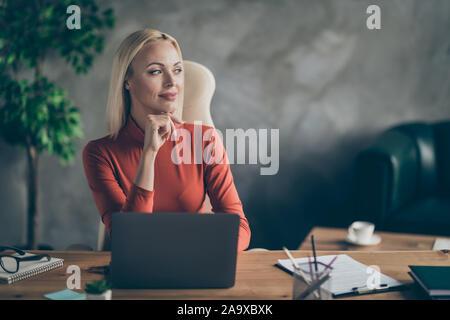 Foto von fröhlichen niedliche verträumte Frau suchen weit weg auf der Suche nach neuen Ideen für Startup sitzen am Tisch mit Laptop auf es - Stockfoto