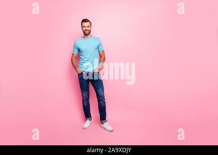 Volle Länge Körper Größe Foto von fröhlichen überzeugter Kerl halten sich an den Händen in Jeans Taschen tragen weiße Schuhe isoliert pastellfarbenen Hintergrund - Stockfoto