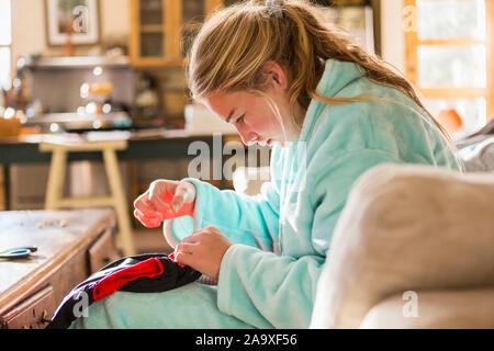 Ein junges Mädchen nähen ein Hemd in Ihrem Bademantel sitzen. - Stockfoto