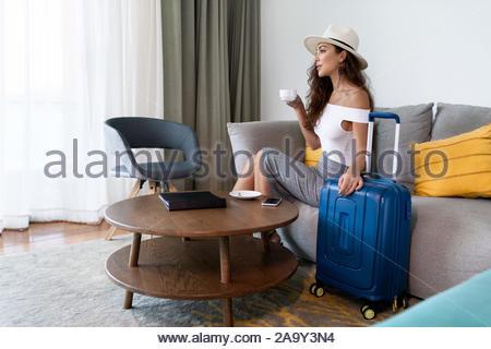 Junge Traveler-Frau in hat keinen Kaffee trinken mit Gepäck im Hotel Zimmer sitzen, schöne Frau warten Entspannung nach Ankunft auf Geschäftsreise - Stockfoto