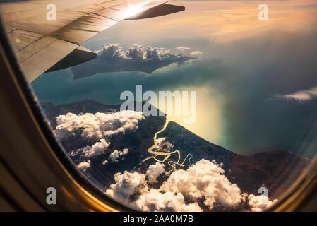 Luftaufnahme aus dem Fenster des Flugzeugs. Fliegen über den Wolken und schönen Land mit River Delta und Meer bei Sonnenaufgang.