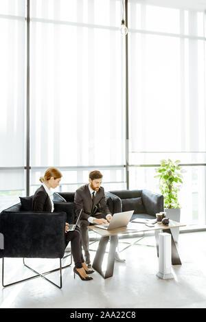 Angestellte von Finanzinstituten arbeiten mit Laptops in der luxuriösen Büro, sitzen auf dem bequemen Sofa in der Nähe der grossen Fenster - Stockfoto