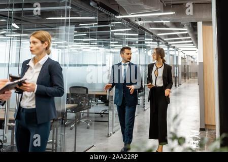 Gruppe von Geschäftsleuten streng gekleidet in den Anzügen treffen im Flur des modernen Bürogebäude, Angestellte in informelle Diskussion im Innenbereich - Stockfoto