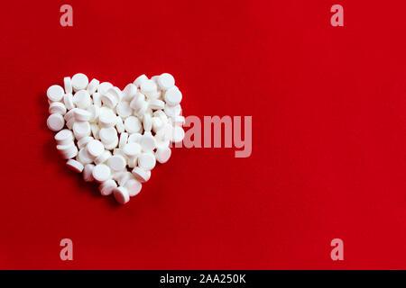 Ein Herz aus kleinen weißen Pillen auf einem roten Hintergrund. Das Konzept der Herzkrankheit. - Stockfoto