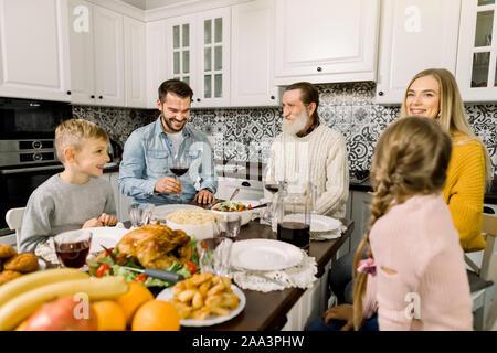 Portrait von groß Familie sitzt am festlich gedeckten Tisch und bei jedem anderen suchen, reden und lächeln. Thanksgiving Dinner Konzept - Stockfoto