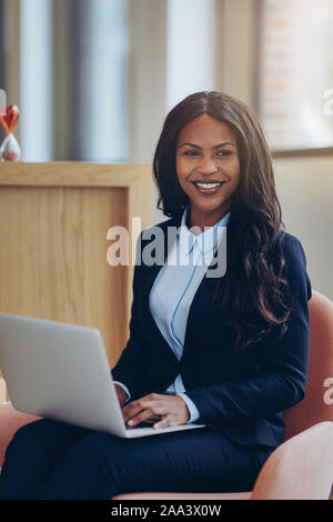 Lächelnden jungen afrikanischen amerikanischen Geschäftsfrau in einem Stuhl sitzend in der Lounge eines modernen Büros arbeiten auf Ihrem Laptop - Stockfoto