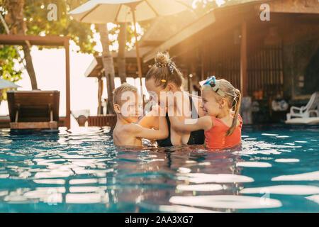 Lächelnde Mutter ihr zwei süssen kleinen Kinder umarmen während Spaß zusammen in einem Schwimmbad in ein tropisches Resort an einem sonnigen Tag - Stockfoto