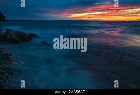Schönen Sonnenuntergang über Green Bay mit wirbelnden Wasser in Bewegung, Streifen über die Felsen und Spritzwasser entlang der Küste in der Nähe von Ellison Bay, Wisconsin, USA - Stockfoto