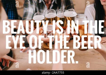 7/8-Ansicht von multikulturellen Freunde klirren Gläser Bier in der Nähe von Schönheit liegt im Auge des Bier halter Abbildung - Stockfoto