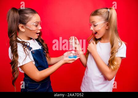 Foto von zwei schönen kleinen Damen fleißig Schule Kinder machen chemische Experiment aufgeregt Ergebnisse Rohr tragen Jeans insgesamt weissen t-shirt halten - Stockfoto