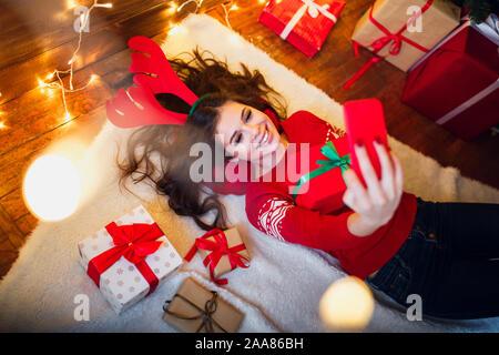 Lächelnde Mädchen eine selfie mit Smartphone und liegen auf dem Boden. Weihnachtliche Stimmung - Stockfoto