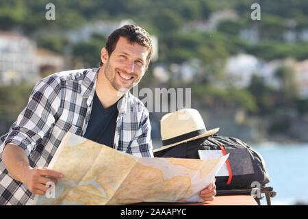 Ihnen gerne touristische Holding Karte betrachtet die Kamera in einer Küstenstadt im Sommerurlaub - Stockfoto