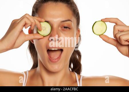 Junge lächelnde Frau mit Scheiben Gurken auf ihre Augen posiert auf weißem Hintergrund - Stockfoto