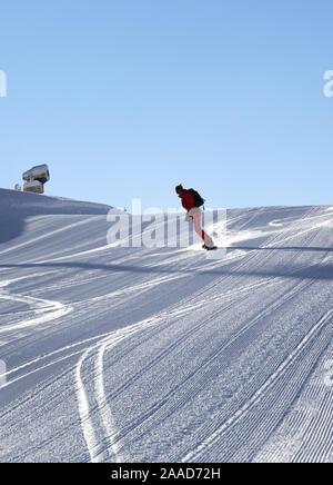 Snowboarder steigt auf verschneiten Skipiste von SNOWCAT am sonnigen Winter Abend zubereitet - Stockfoto