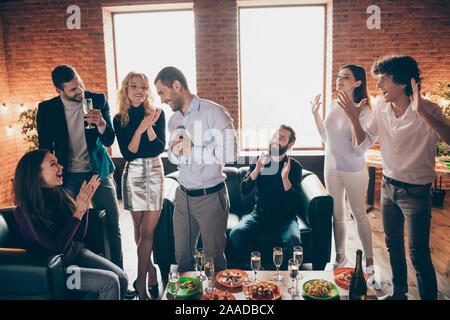 Erstaunliche Stimme. Foto von besten Freunden feiern Neujahr party Karaoke singen Lieder halten Mikrofon klatschen Verschleiß formalwear sitzen Sofa