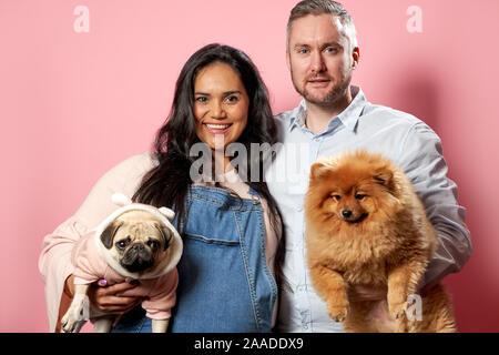 Junge schwangere Frau und Mann halten sie Hunde auf Händen auf rosa Hintergrund im Studio - Stockfoto