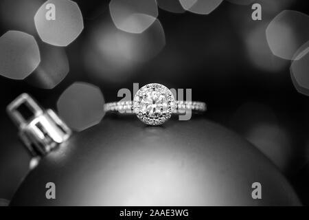 Verlobungsring auf a Christmas Ornament mit Licht im Hintergrund. Schwarz und Weiß. - Stockfoto
