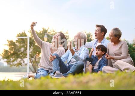 Drei generation gerne asiatische Familie sitzt auf Gras, eine selfie mit Handy draußen im Park - Stockfoto