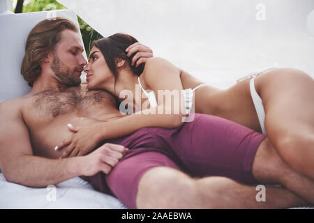 Schöne junge Paar in Badebekleidung am Strand gegen eine sand Lächeln und Umarmung. - Stockfoto