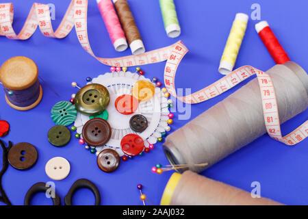 Nähen Knöpfe und Threads auf einem blauen Hintergrund. Handarbeit Konzept. Viele bunte kleine Spulen von Nähgarn auf gelbem Hintergrund. Sk - Stockfoto