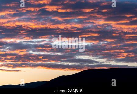 Wolken verfangen der Letzte Abendsonne und orange leuchtende, oberhalb der Yorkshire Dales in Wensleydale, UK. Stockfoto