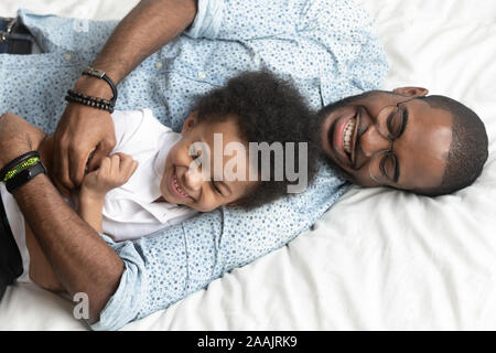 Ansicht von oben liebenden Vater kitzelt kleinen Sohn liegend auf Bett - Stockfoto