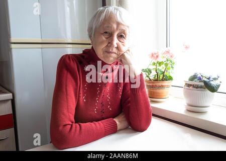 Ältere einsame Frau gedrückt Sitzen am Tisch
