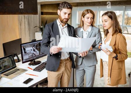 Kleine Gruppe von kreativen Mitarbeiter arbeiten mit einem Projekt auf die Blaupausen, die während der Sitzung in das moderne Büro von Architekturbüro - Stockfoto