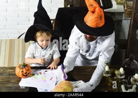 Halloween und Urlaub Konzept. Mann und der Junge im Zimmer am weißen Stein Hintergrund. Witcher und wenig Magier machen Sie sich bereit für Halloween. Mann und Kind mit langen Gesichtern in der Hexe Hüte ziehen und dekorieren Kürbisse - Stockfoto