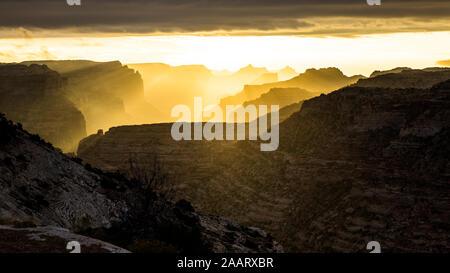 Sonnenaufgang in der Wüste von Utah Beleuchtung bis Schichten von felsigen Klippen Mesas, Buttes und Türme Gegenlicht der Morgenlicht. - Stockfoto