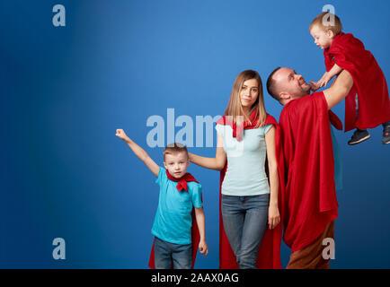 Glückliche Mama und Papa, Kinder Superhelden in roten Mänteln auf leeren blauen Hintergrund im Studio - Stockfoto