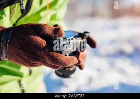 Mann Einrichten der Kamera. Fotograf nimmt Bilder von Winter Wald landschaft.
